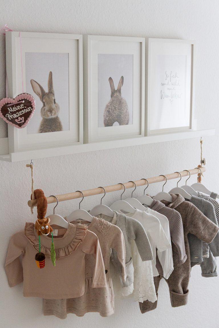 Cabideiro simples na prateleira decorada com quadros e cômoda abaixo