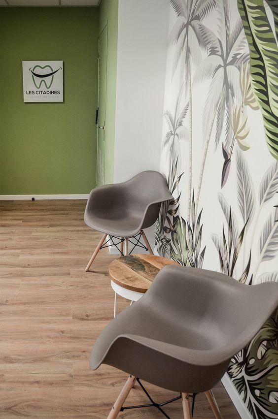Consultório dentário com sala de espera decorada com papel de parede de plantas e cadeira cinza