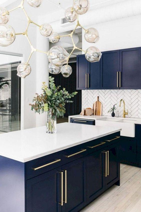 Cozinha azul com silestone branco e detalhes em dourado na decoração