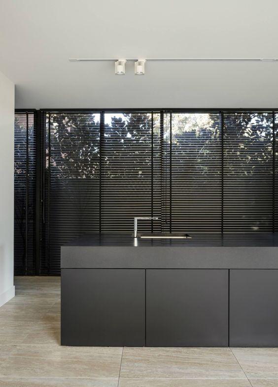 Cozinha com armários cinza e persiana preta