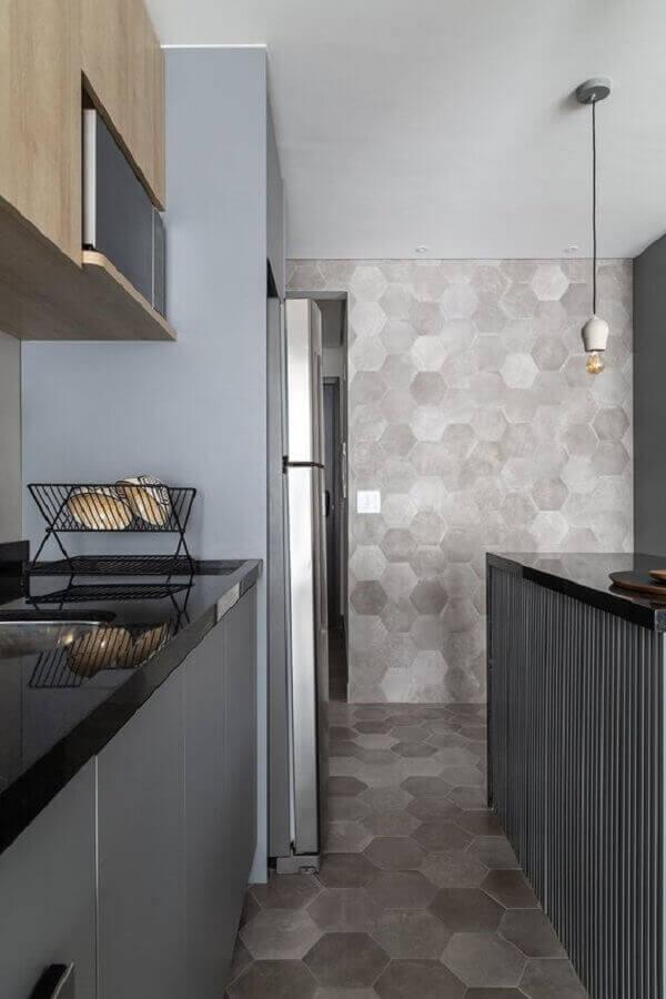 Cozinha moderna com revestimento cerâmico cinza que se estende do piso para a parede. Fonte: MSAC Arquitetura