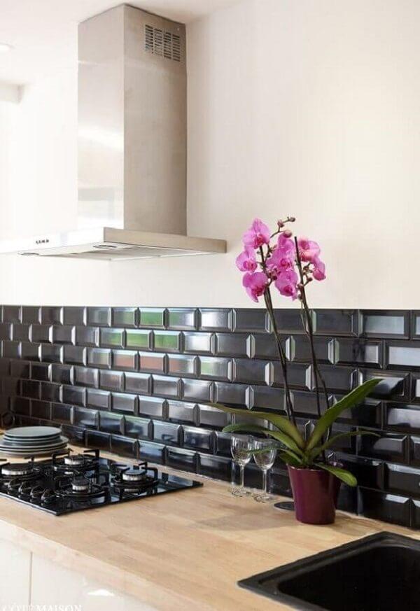 Cozinha rústica com bancada de madeira e revestimento cerâmico preto na parede. Fonte: Duas Arquitetura