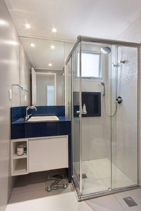 Decoração clean com pedra para bancada azul marinho e armário de banheiro com pia pequeno branco