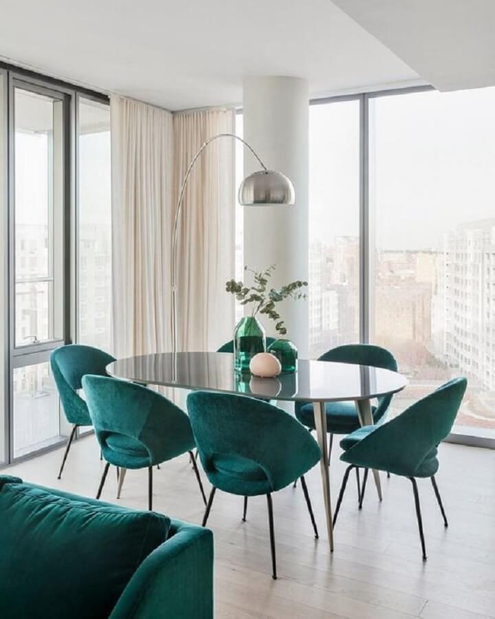 Decoração clean para sala de jantar com mesa oval preta e cadeira estofada verde Foto Curated Interior