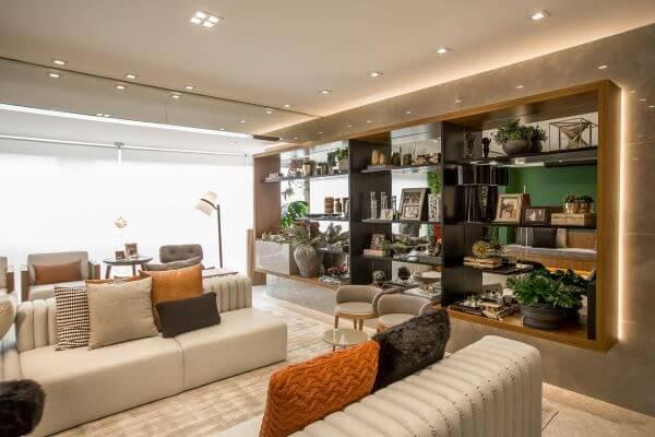 Decoração da sala grande decorada com estante iluminada e sofá