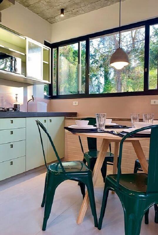 Decoração de cozinha com mesa redonda de madeira e cadeira verde escuro Foto Archtrends