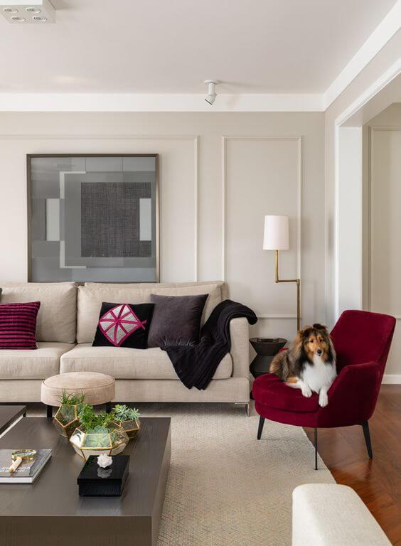Decoração de sala clássica com parede decorada com moldura de gesso e quadro em tons de cinza