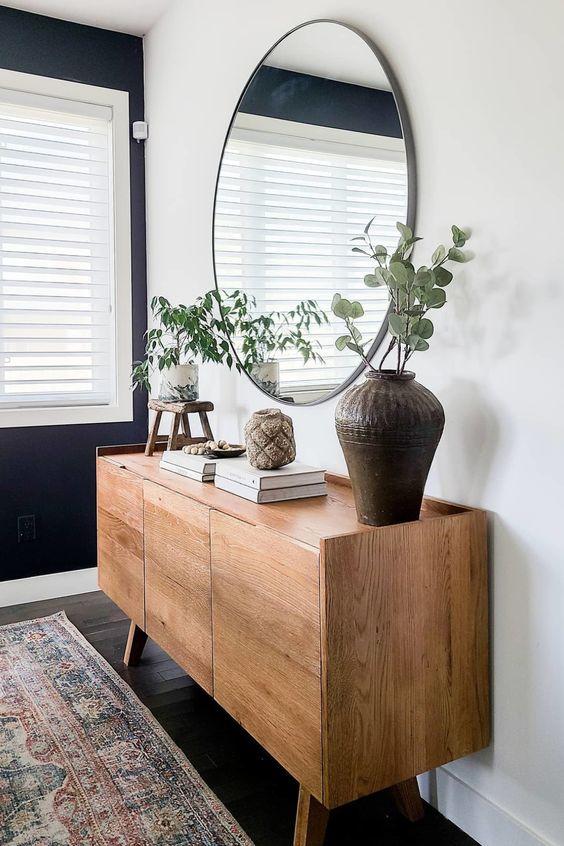 Decoração moderna com aparador de madeira e espelho redondo preto