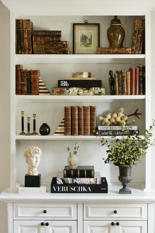 Enfeites para estante com livros e vasos de flores