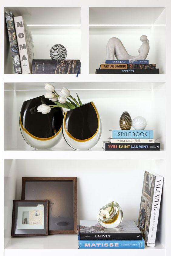 Enfeites para estante com vasos pretos e livros