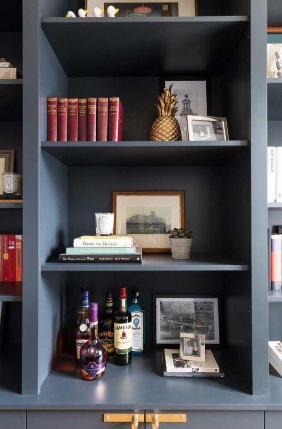Enfeites para estante variados com bebidas livros e fotos