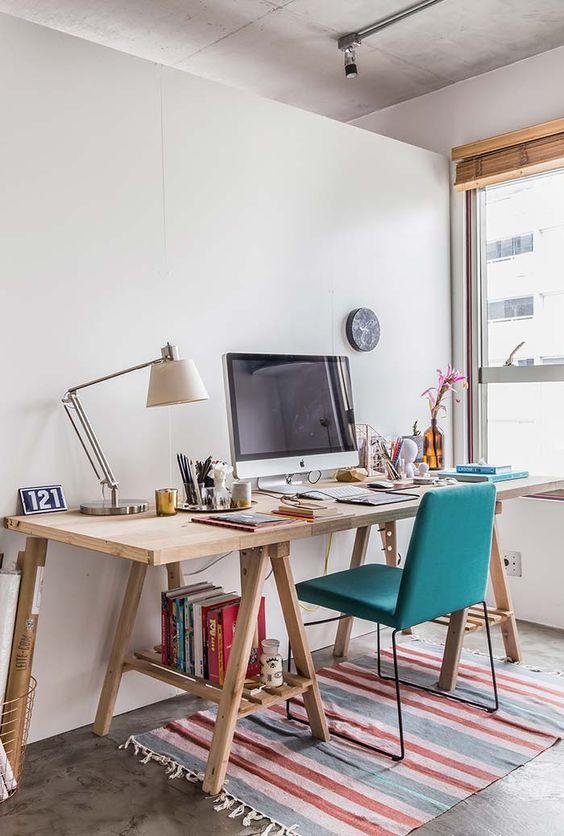 Escritório com mesa de cavalete e cadeira turquesa moderna