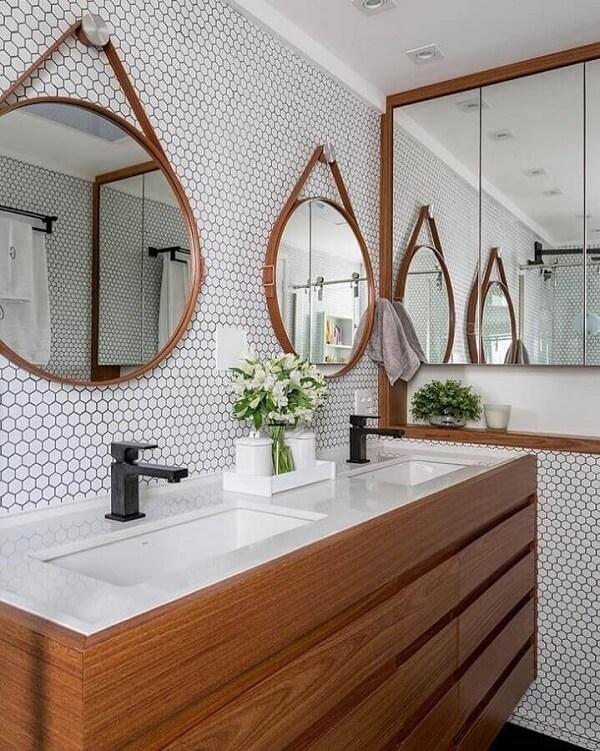 Espelho adnet e revestimento cerâmico hexagonal branco decoram o banheiro. Projeto de Estúdio AE Arquitetura