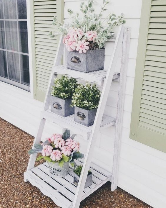 Estante cavalete branca para jardim decorado com flores