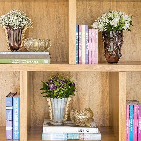 Estante decorada com livros e vasos de flores
