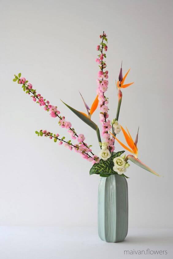 Flores coloridas ikebana com vaso verde claro