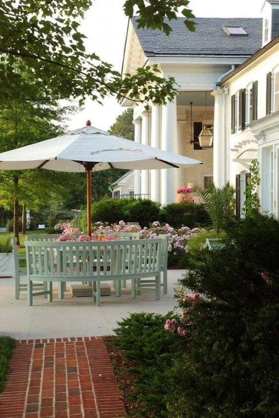 Guarda sol para piscina com mesa e cadeiras verdes perto do jardim