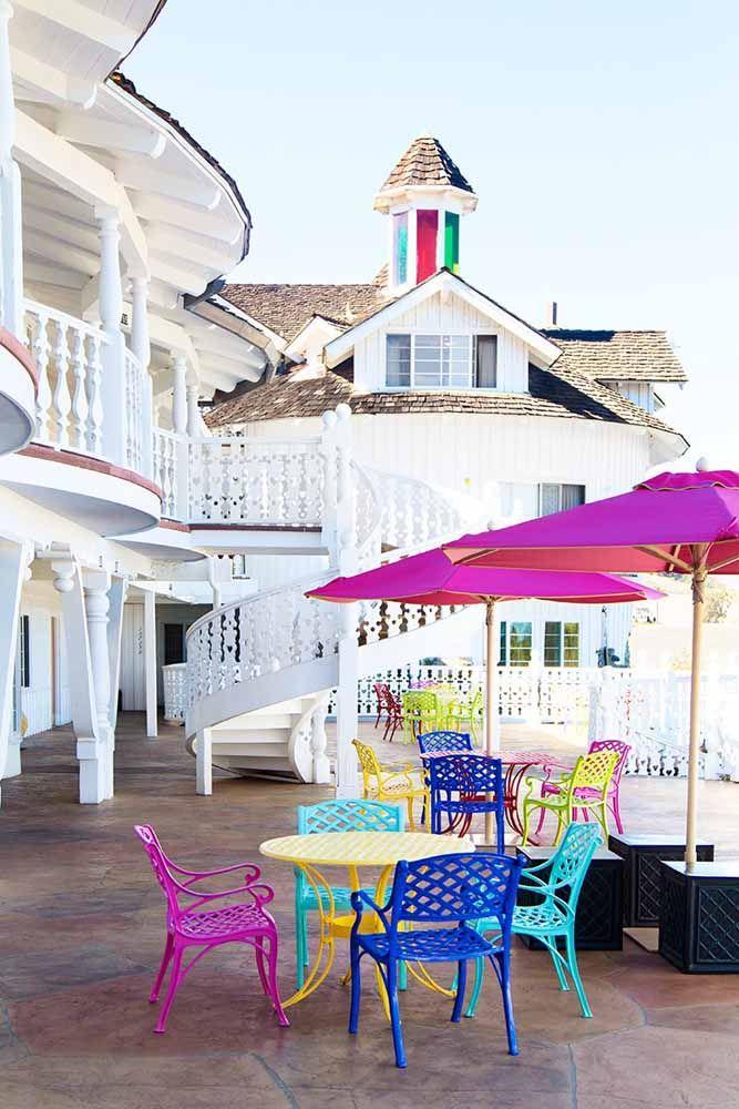 Guarda sol para piscina em cor de rosa com mesas e cadeiras coloridas