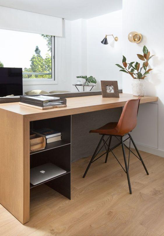 Home office na sala com escrivaninha de madeira e cadeira de couro