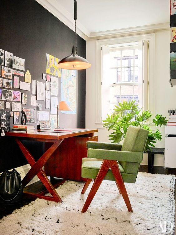 Home office na sala com mesa de madeira e cadeira verde