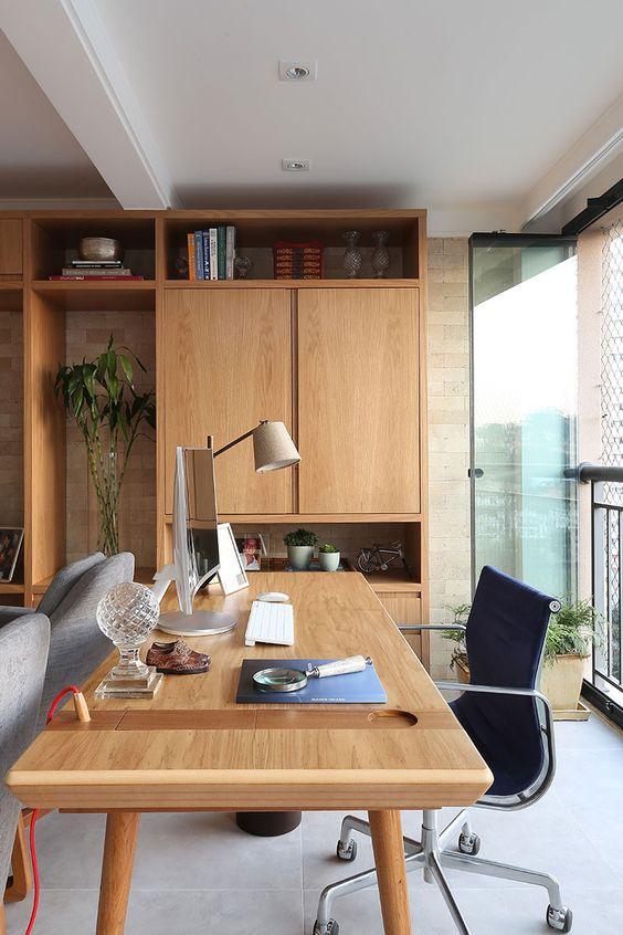 Home office na sala com mesa grande de madeira e cadeira giratoria preta