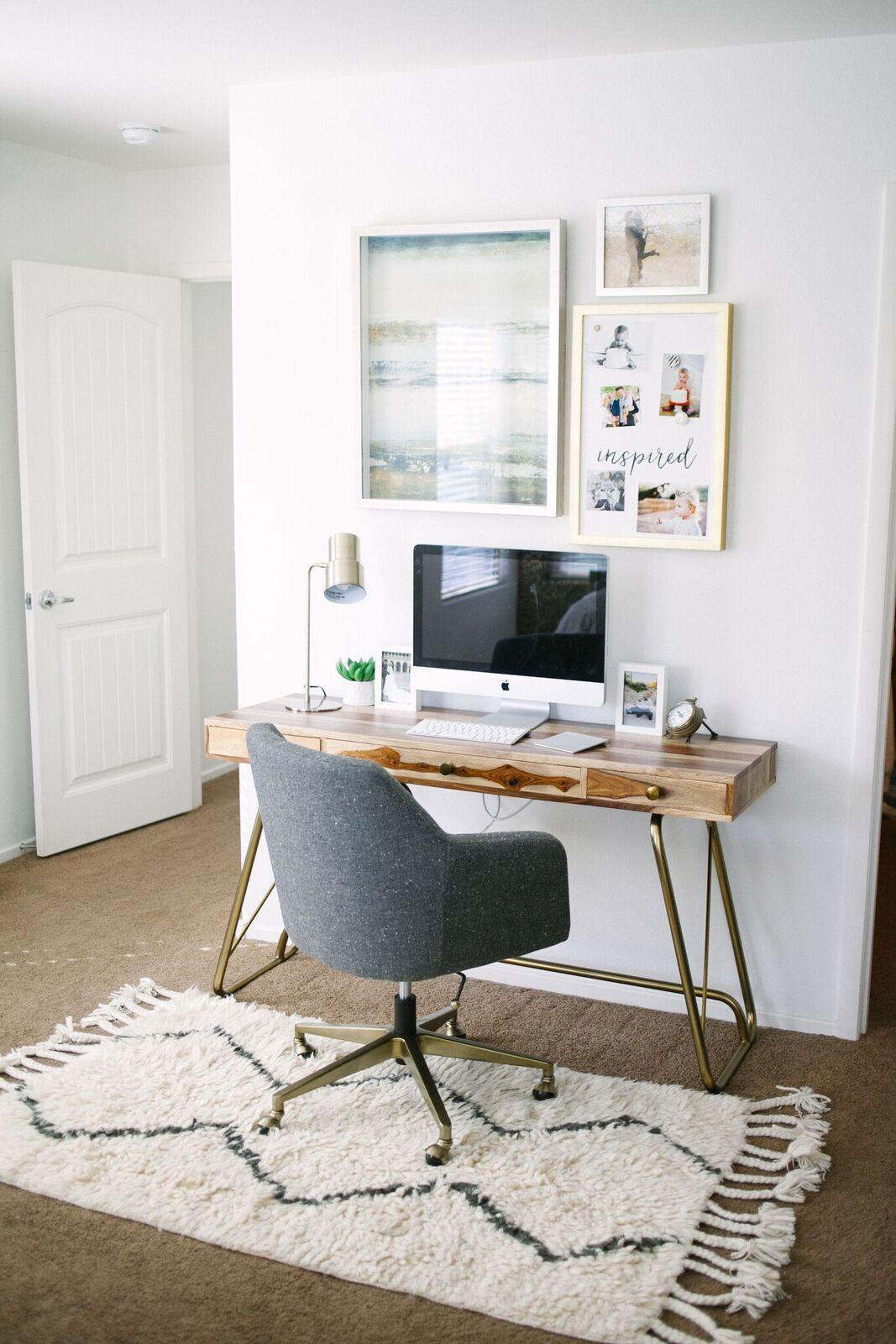 Home office na sala de estar com mesa de madeira e cadeira cinza