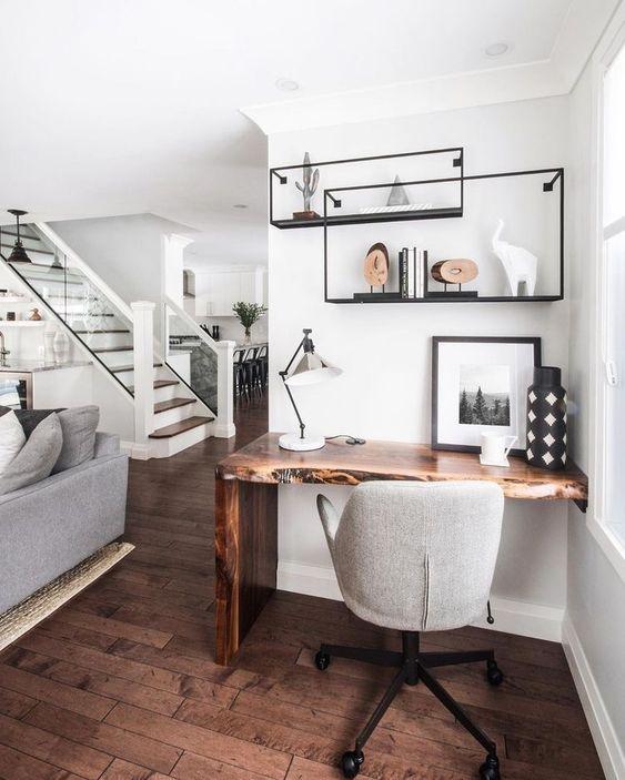 Home office na sala de estar com mesa de madeira rustica e cadeira giratoria cinza