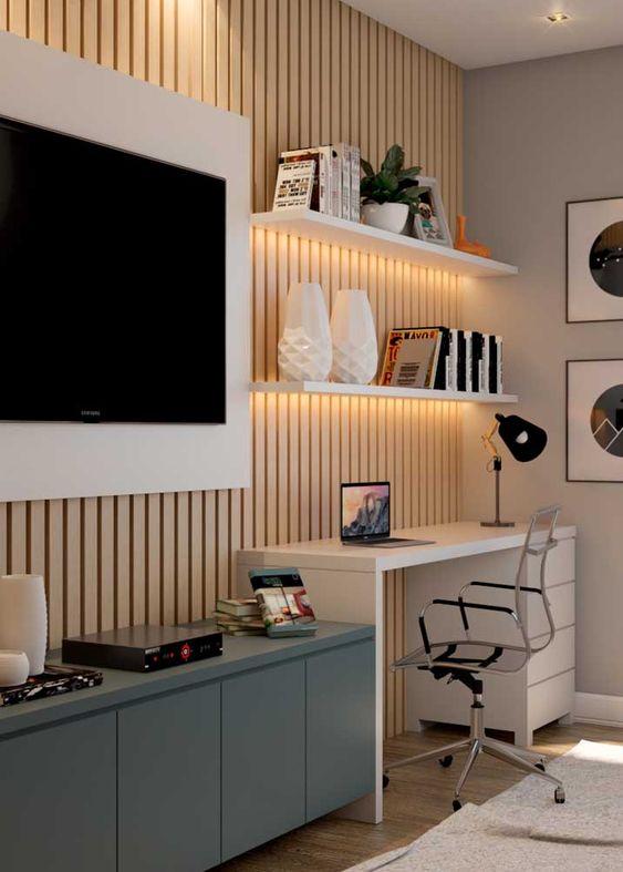 Home office na sala de estar planejada com rack escrivaninha branca e painel para tv
