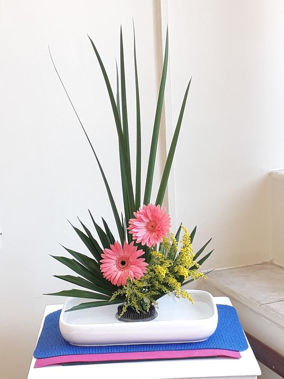 Ikebana Sanguetsu com flores cor de rosa e folhas altas