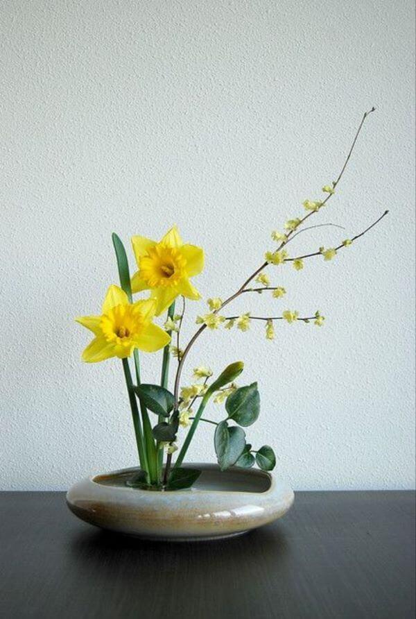 Ikebana com flores amarelas e vaso pequeno