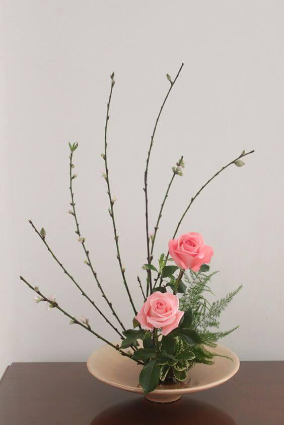Ikebana com flores rosa e detalhes delicados