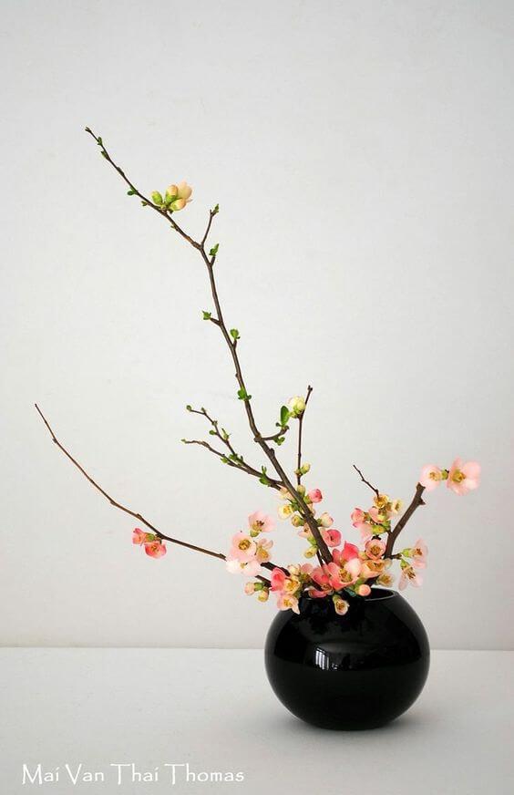 Ikebana com vaso preto e flores cor de rosa