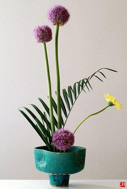Ikebana delicada com vaso azul e flores em roxo e amarelo