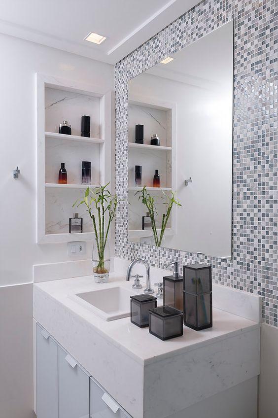 Nicho de embutir para banheiro com pastilhas ao redor do espelho
