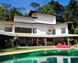 O móvel em tom vermelho se destaca na área de lazer com revestimento piscina verde. Projeto de Olegário de Sá & Gilberto Cioni