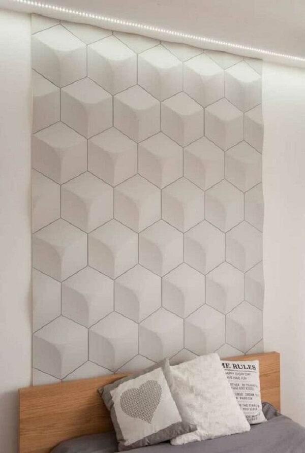 O revestimento cerâmico 3D branco se estende da cabeceira da cama até o teto. Fonte: Pinterest