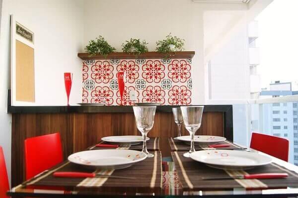 O revestimento cerâmico com nuances em vermelho se conecta com as cadeiras da mesa. Projeto de Priscila Fernandes Arquitetura