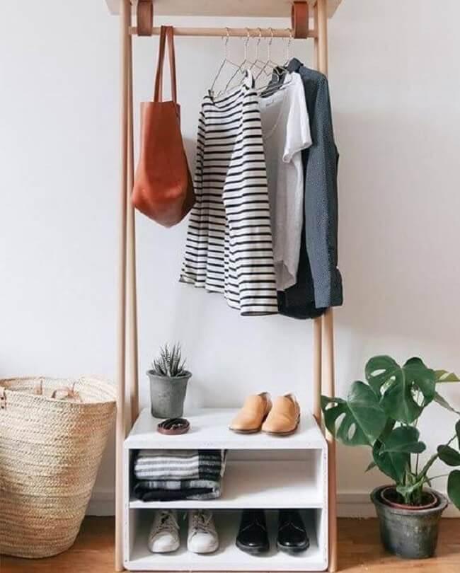 Organize sapatos e roupas de cama na arara de roupas de madeira. Fonte: Decostore