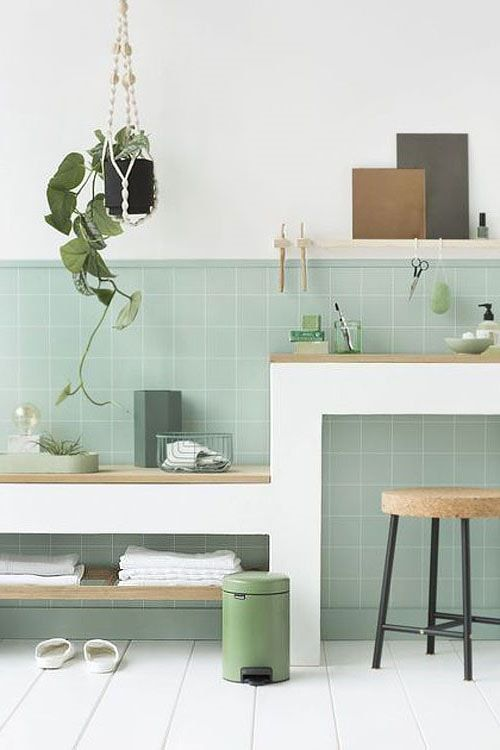 Parede de sala decorada com azulejo verde claro e plantas suspensas