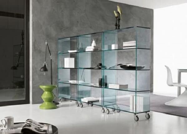 Parede cimento queimado e estante de vidro com rodízios complementa a decoração. Fonte: Pinterest