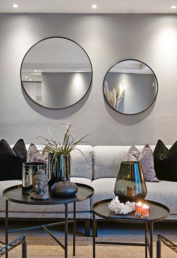 Parede de sala decorada com espelhos redondos com moldura preta