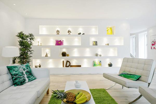 Parede de sala decorada com estante de gesso iluminada