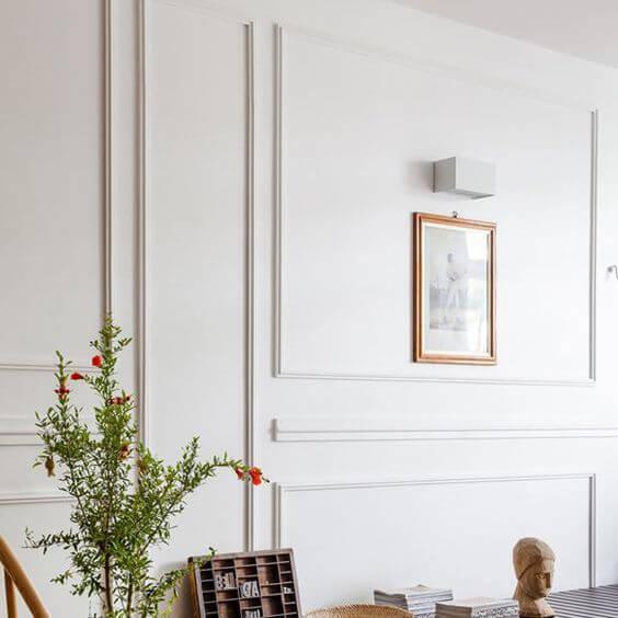 Parede de sala decorada com moldura de gesso e quadros delicados