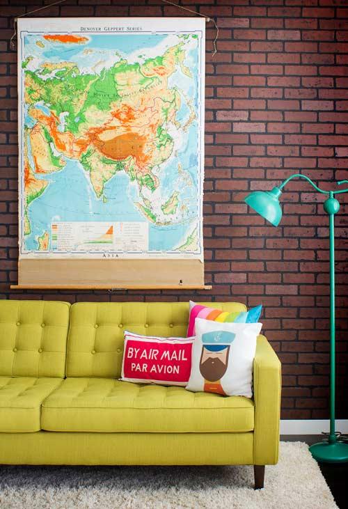 Parede de sala decorada com papel de parede de tijolinho e quadro de mapas coloridas com almofadas divertidas no sofá amarelo
