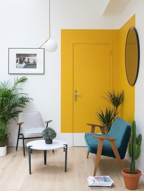 Parede de sala decorada com pintura setorizada em amarelo