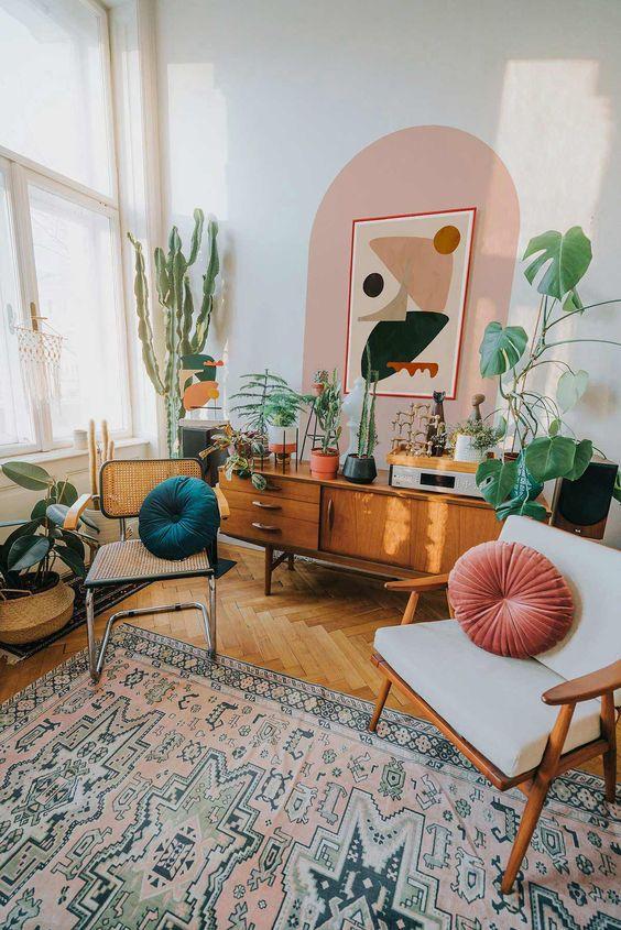 Parede de sala decorada com pintura setorizada em rosa claro e móveis confortáveis