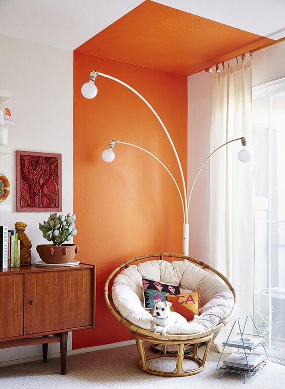 Parede de sala decorada com pintura setorizada laranja perto do rack de madeira e poltrona de ratan