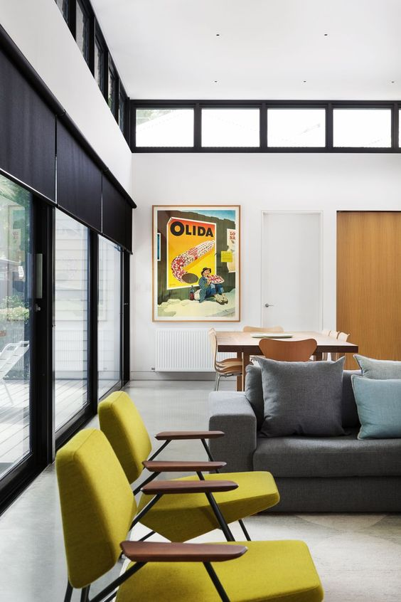 Parede de sala decorada com quadros coloridos que combinam com os móveis