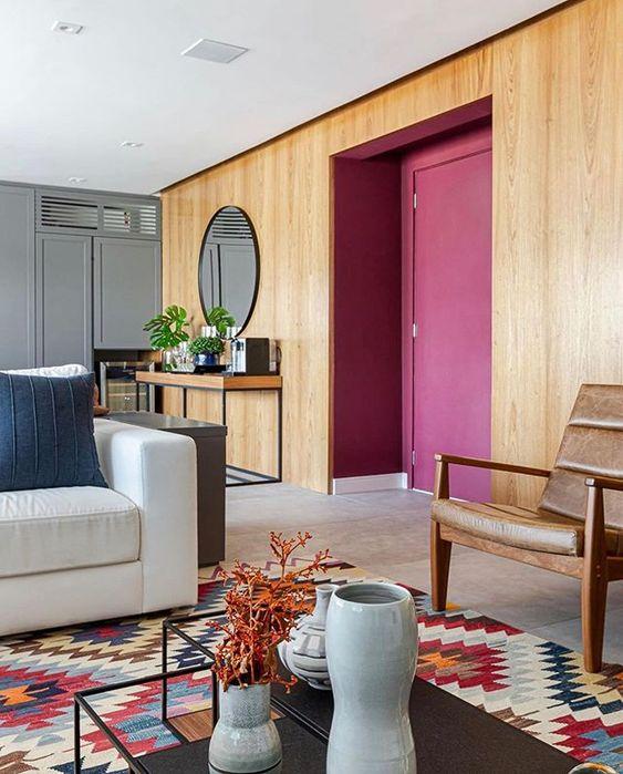 Parede de sala decorada com revestimento de madeira e porta de madeira pintada de marsala