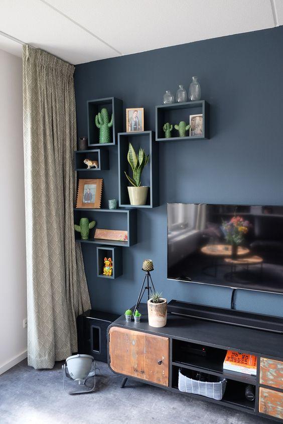 Parede de sala decorada com tinta azul e nichos da mesma cor para decorar com plantas